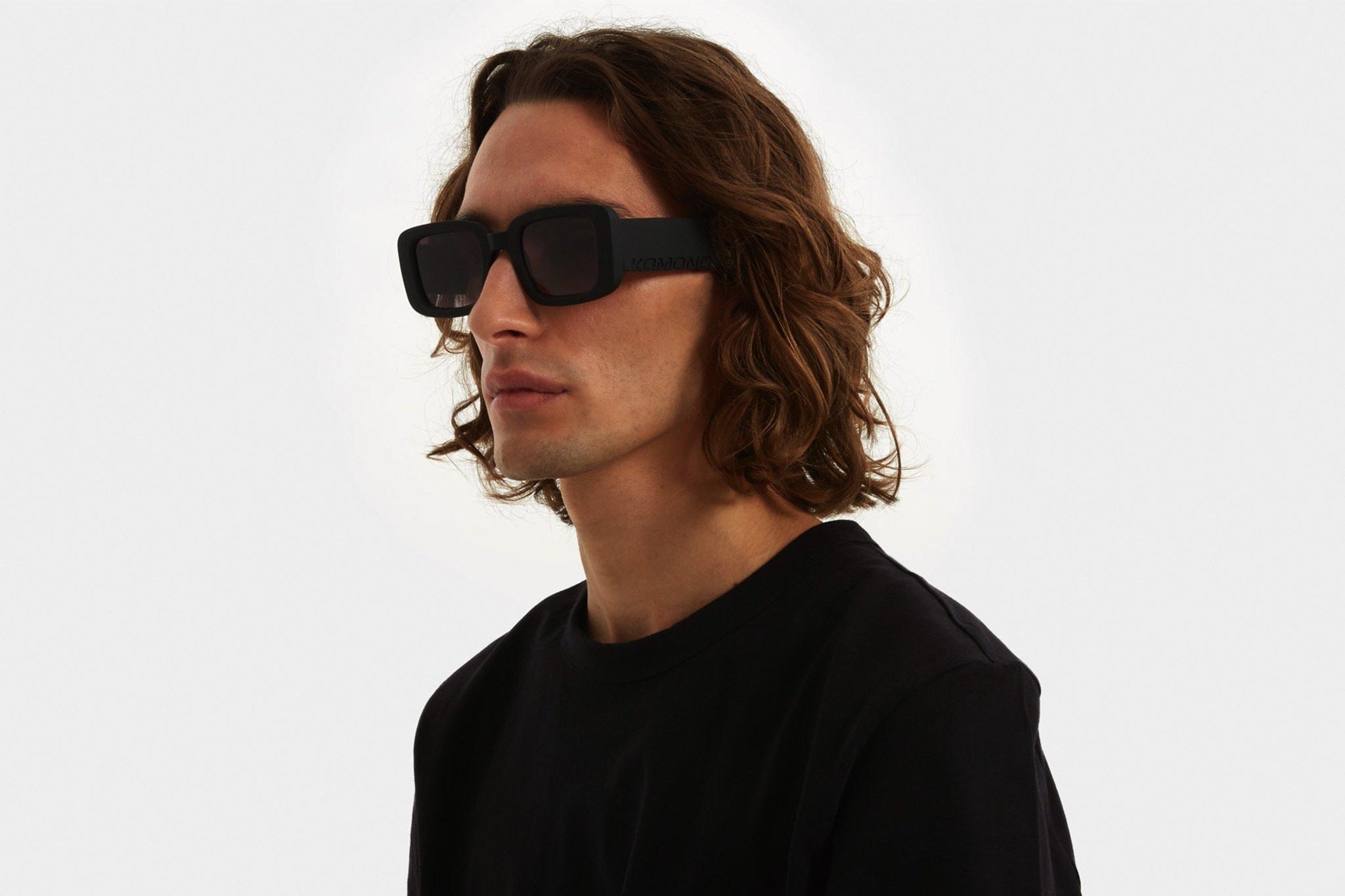 Ανδρικά και γυναικεία κοκάλινα τετράγωνα γυαλιά ηλίου Komono Avery Carbon σε μαύρο ματ σκελετό και γκρι ντεγκραντέ φακούς για όλα τα πρόσωπα.